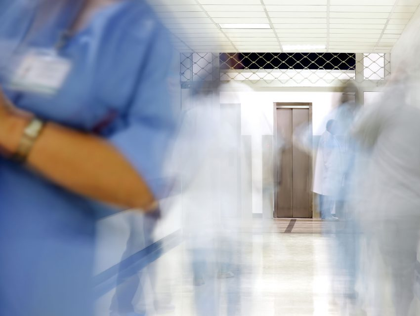 Blurred hallway with medical professionals in a hospital